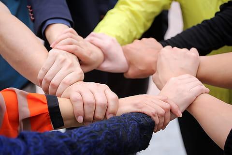 Händer som hjälper varandra, formar en sammanhållande ring, för samverkan och stöd till varandra