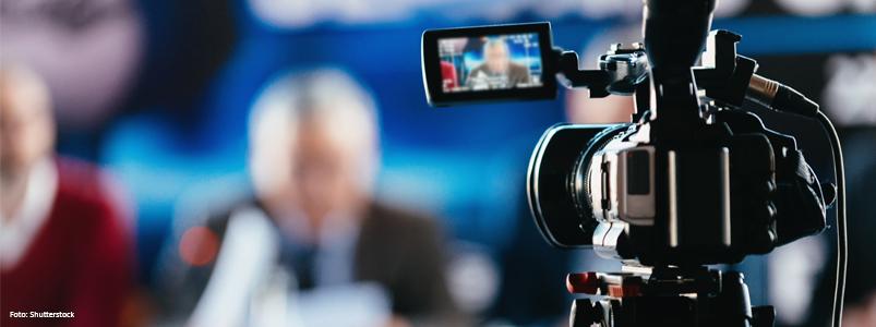En filmkamera med ett suddigt motiv i bakgrunden