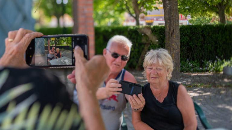 En person tar kort med mobiltelefon på två äldre personer som skriver på en mobiltelefon