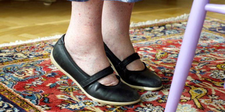 Bild på fötterna med svarta skor på en äldre person