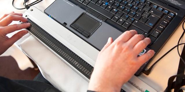 En person som använder en punktskriftstangentbord vid datorn.