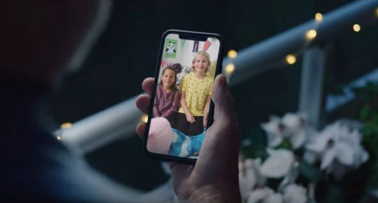 Morfar håller i en smart telefon där han ser barnbarnen i en digital kommunikationstjänst